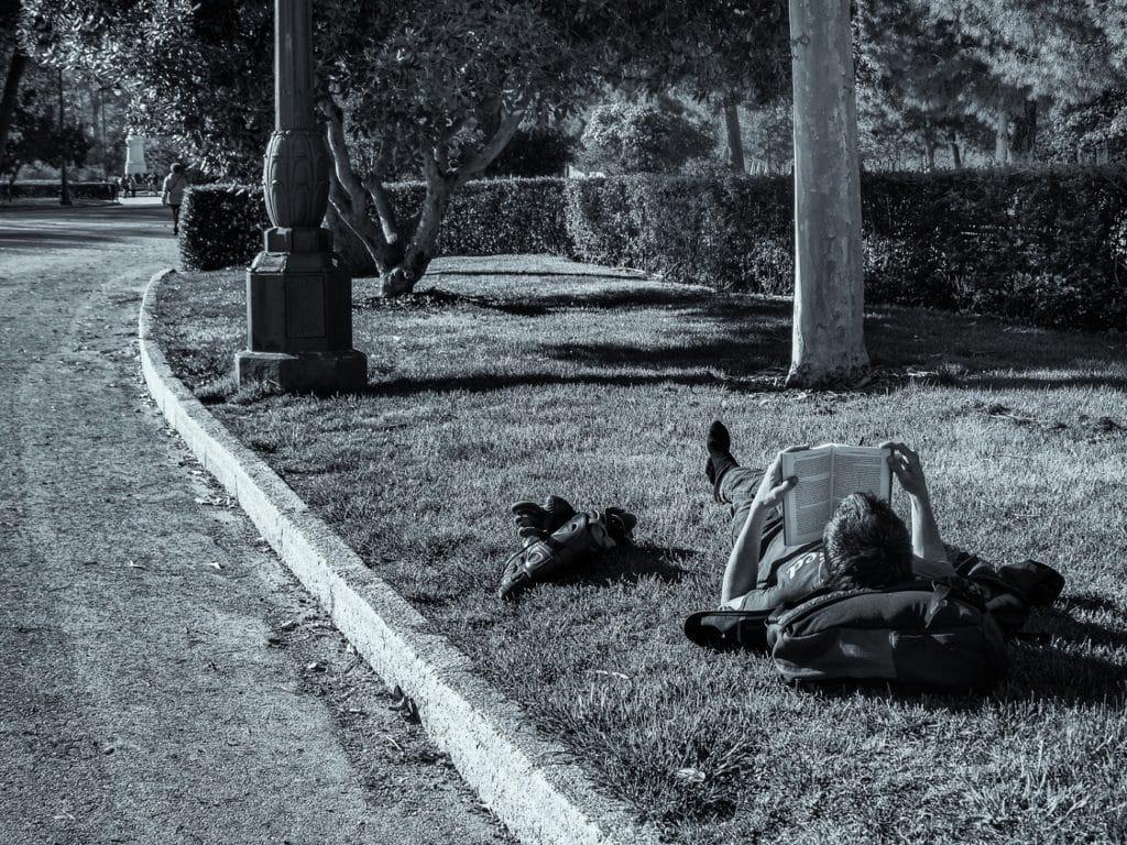 Chico leyendo en un parque. Niko López.