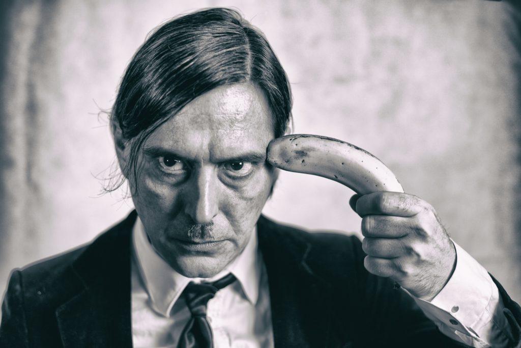 Hombre con un plátano en la sien. Fotografía en blanco y negro de Ada Crow.