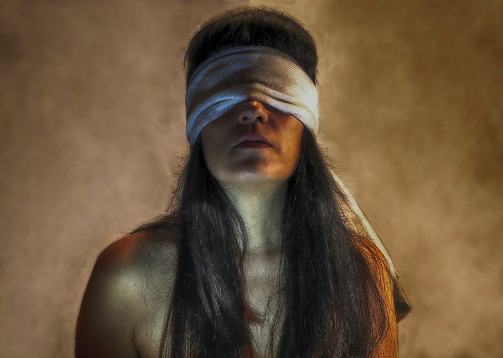 Fotografía mujer con venda en los ojos de Ada Crow.