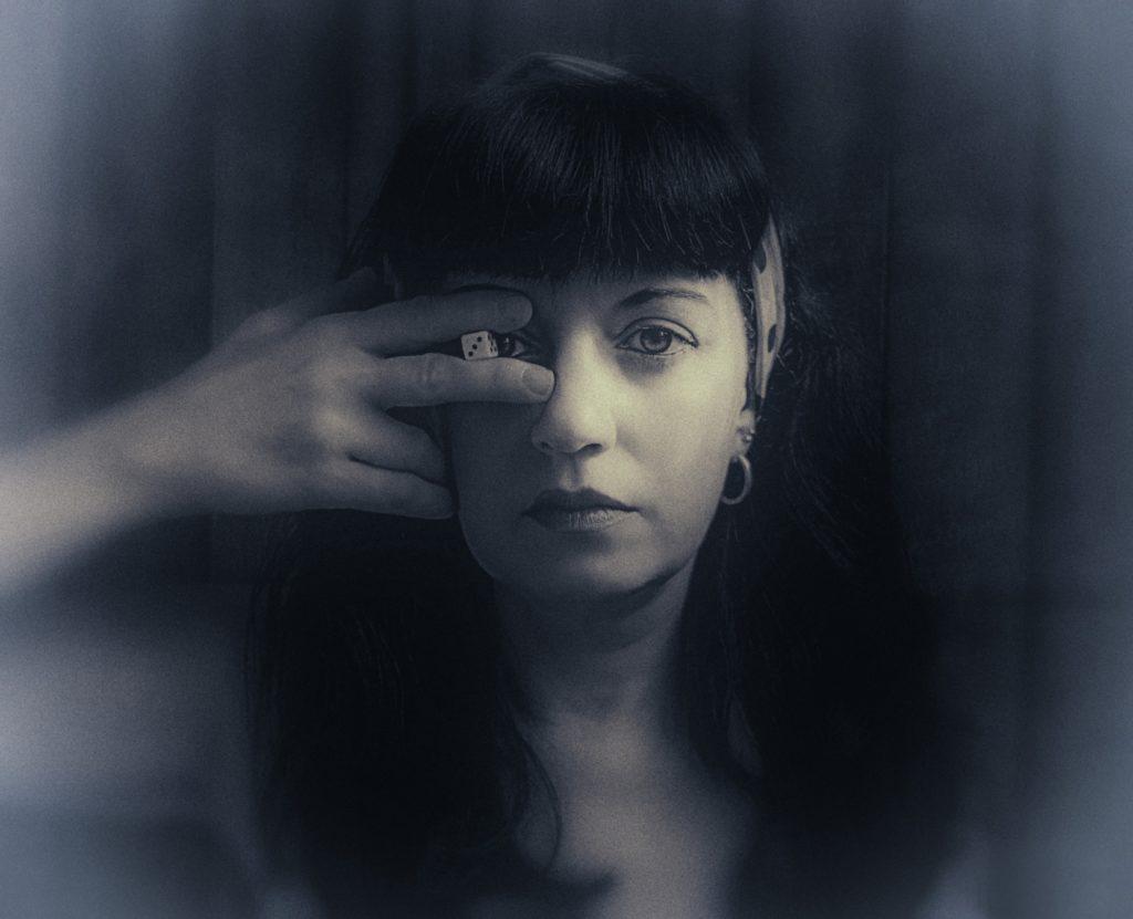 Mujer con dado en un ojo. Fotografía en blanco y negro.